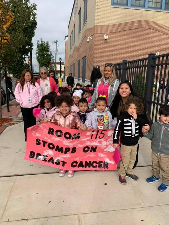class holding their banner that says room 115 stomps on breast cancer