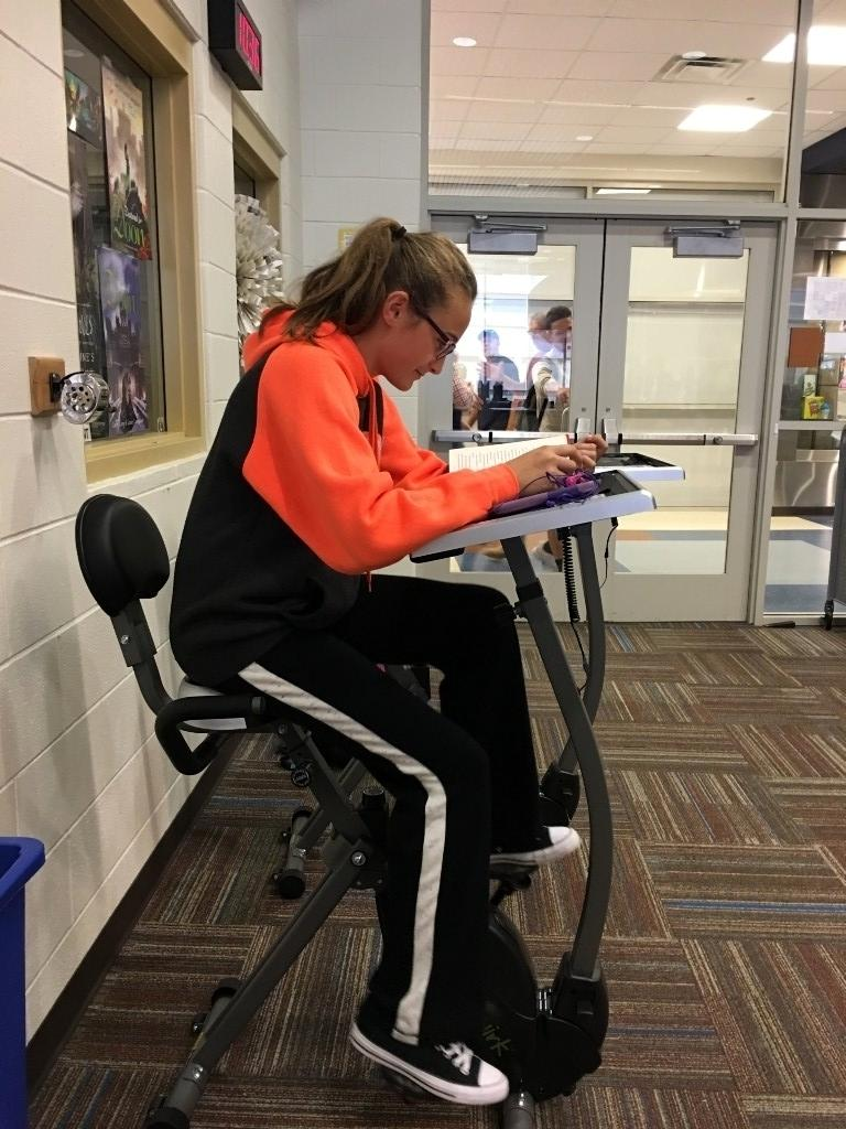 Student reading on a treadmill