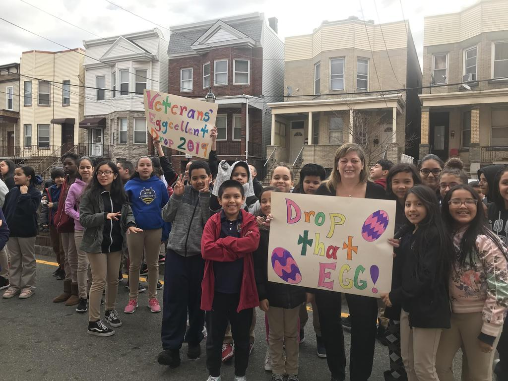 "students with Mrs. Amar holding a sign ""Drop that Egg"" and ""Eggcellent Drop"""