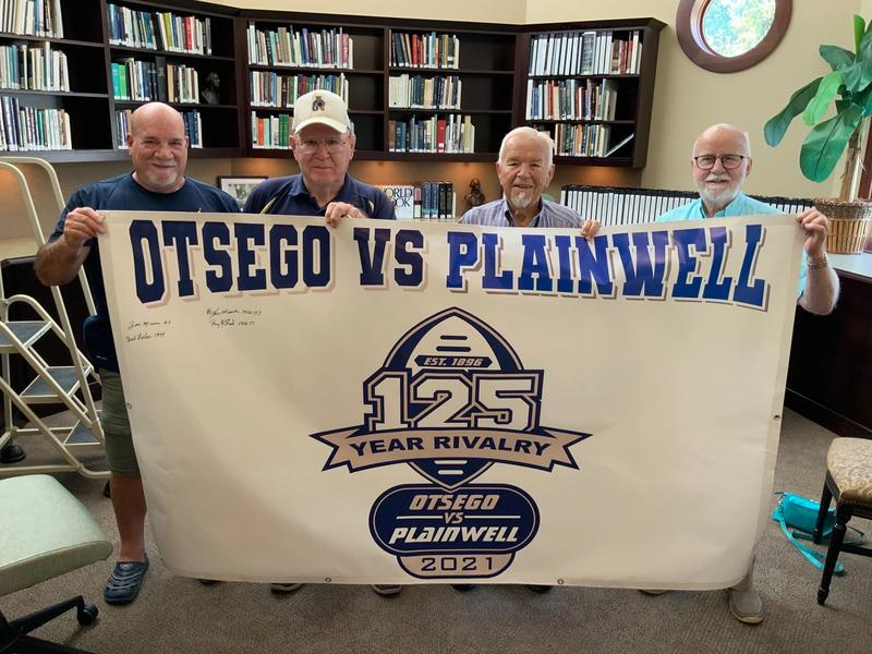 Bulldog football players of the stand with a banner for the anniversary game.