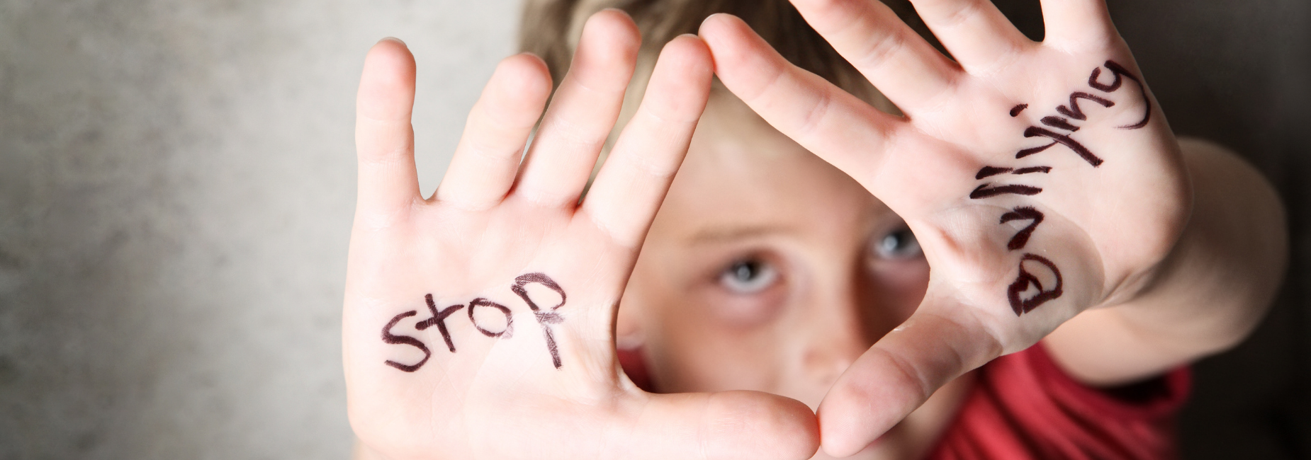boy holding up hands with stop bullying written on his palms