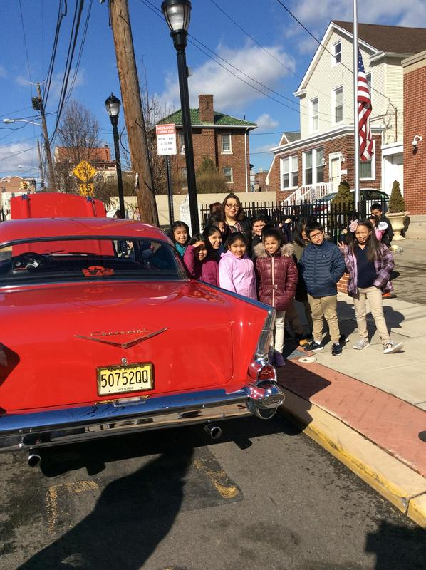 Student and Ms. Menjivar next to the 57 Chevy