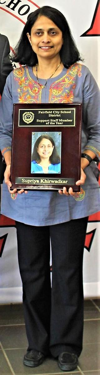 A photo of Supriya Khirwadker the Support Staff Member of the Year. She is holding a plaque with her photo on it,