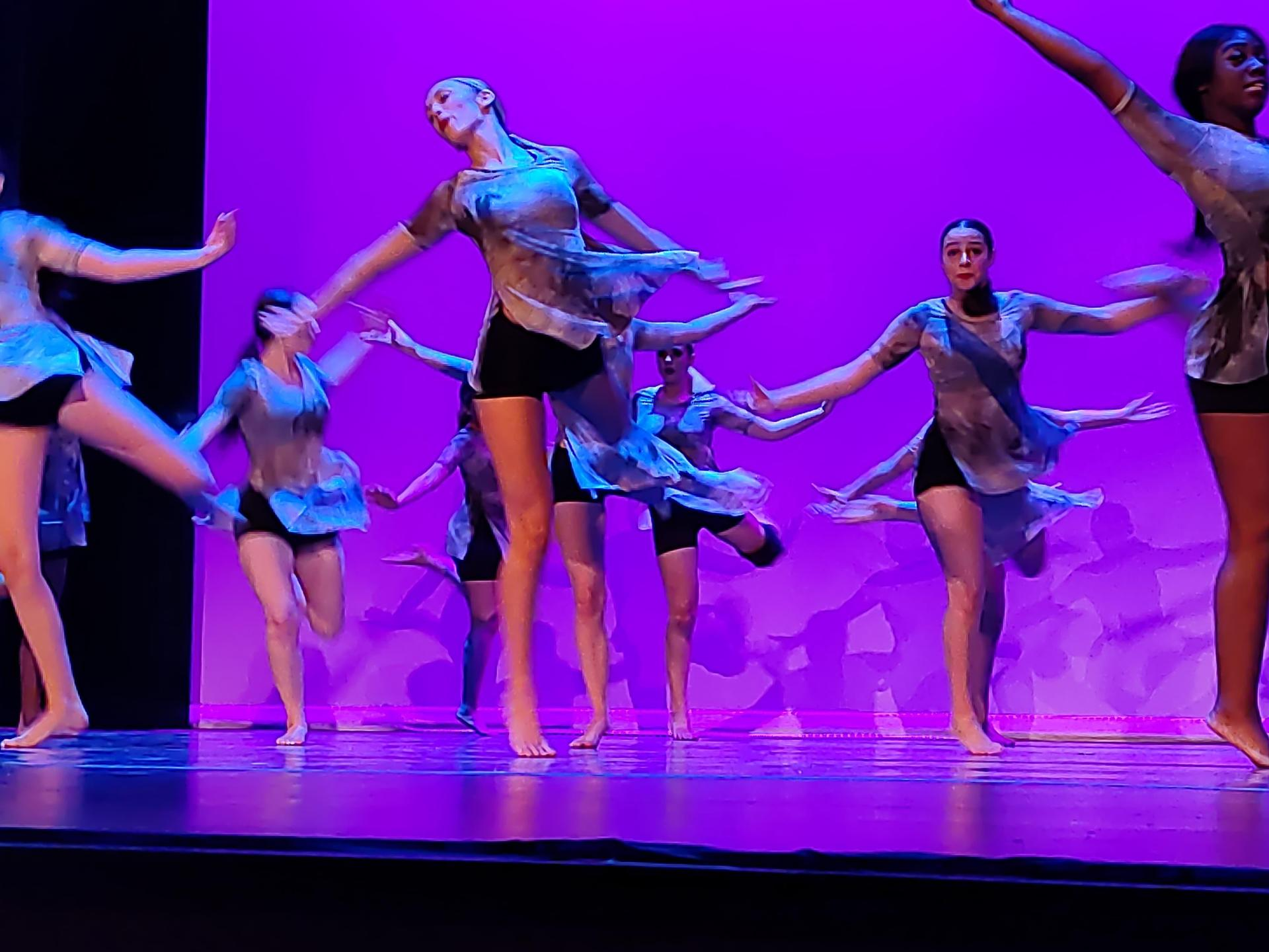 Dancers with pink background with tie dyed tops performing a jump.