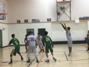 basketball player taking a free throw shot with other players lined up by the basket