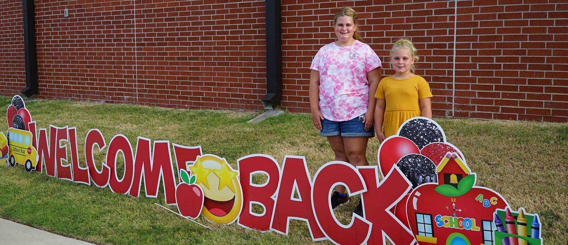 Students next to 'Welcome Back' sign