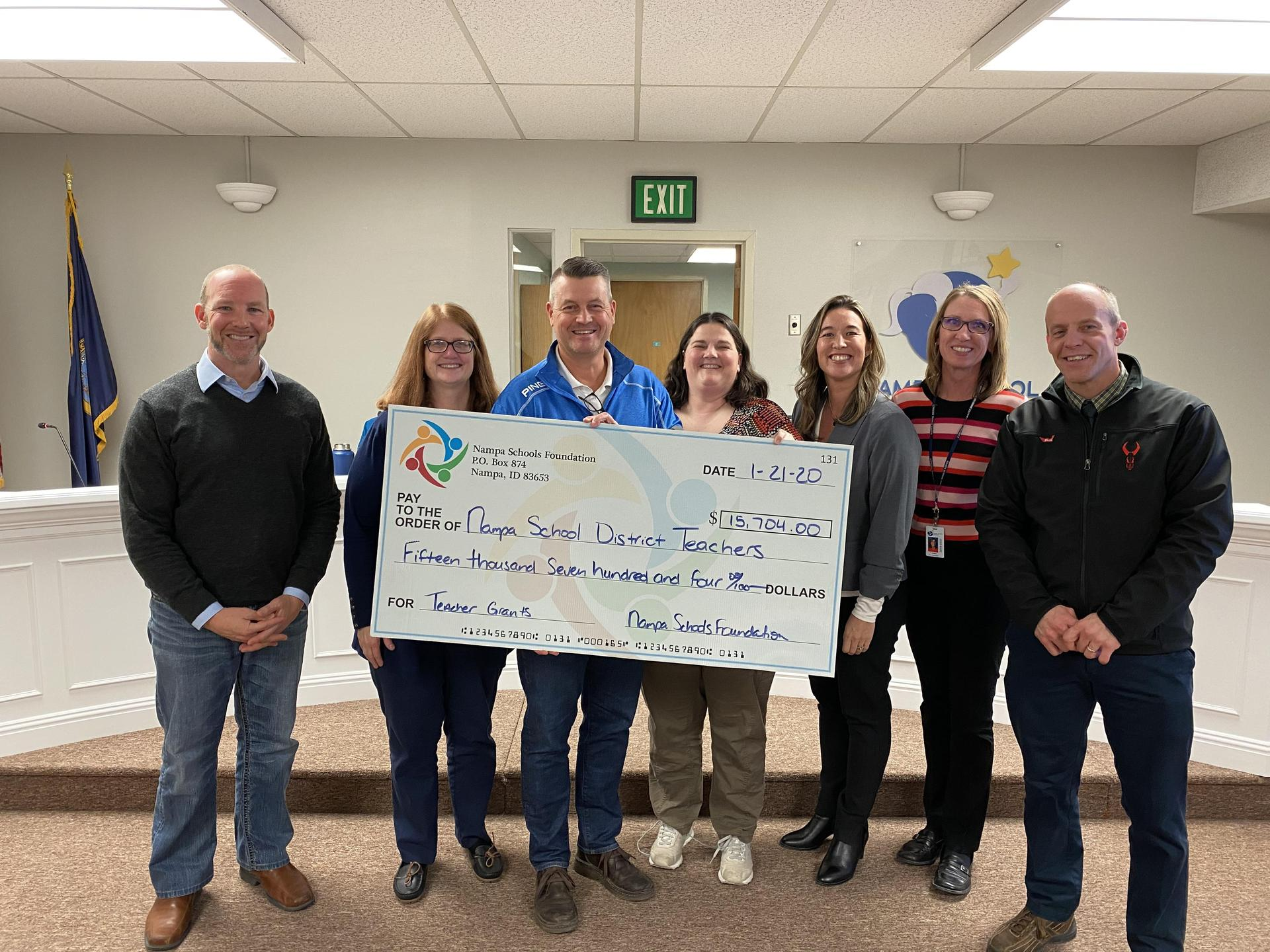 Board Trustees accept a large check from Nampa Schools Foundation board members.