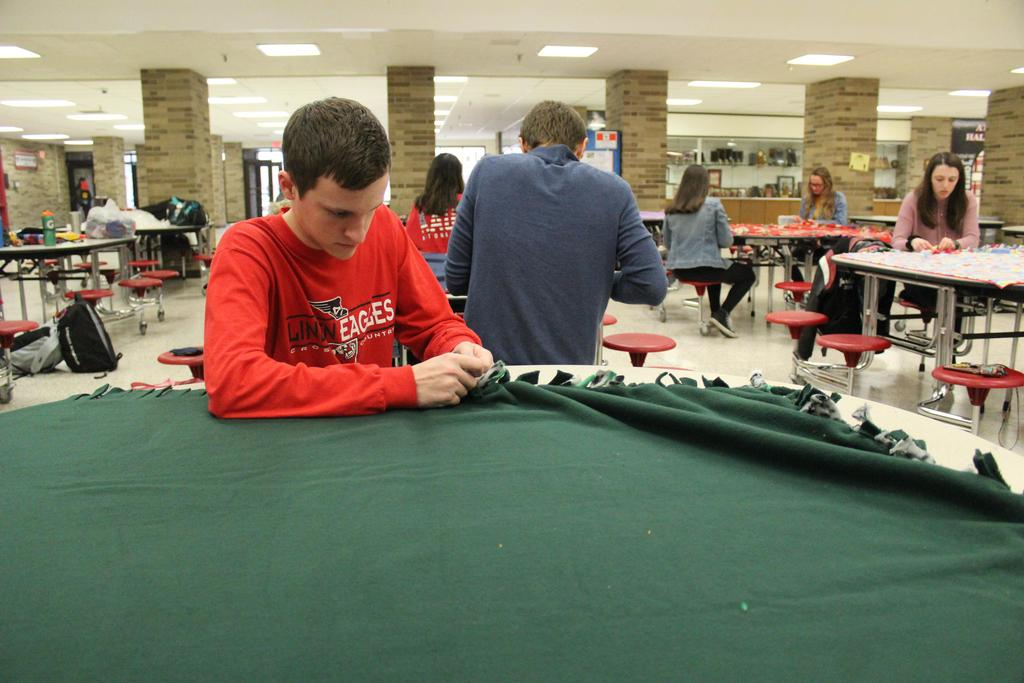 Students sitting at tables tying fleece blankets together