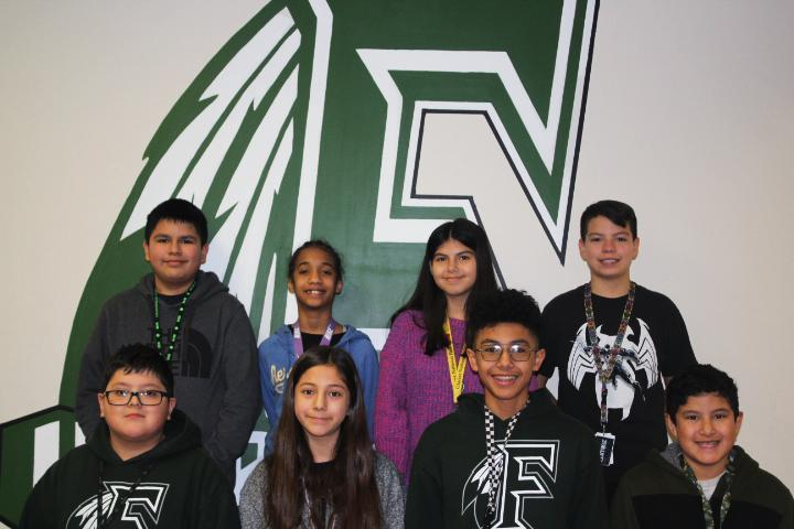 group of 6th grade students pose in front of school logo