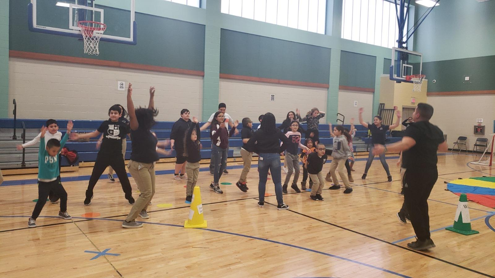 a group of children dancing and jumping up and down in the gym
