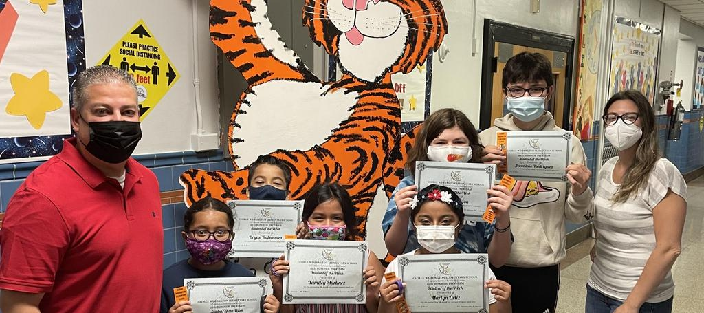 Students of the week posing with large tiger cutout