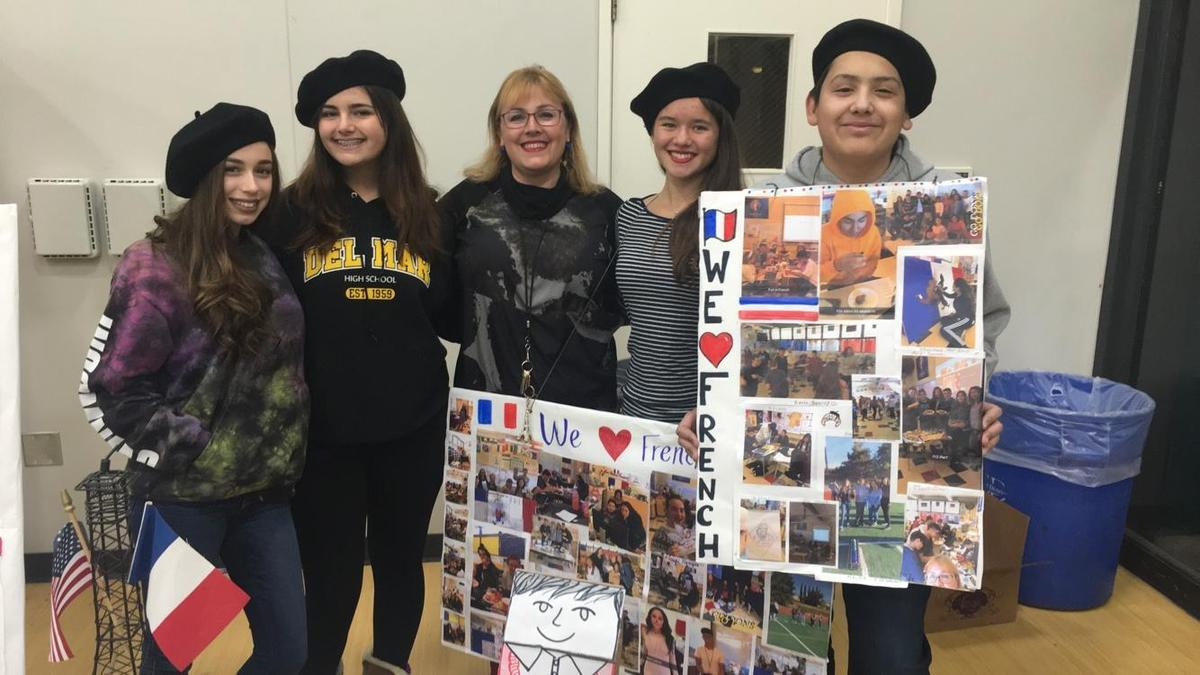 Image of Mme Saade and French students showing their project