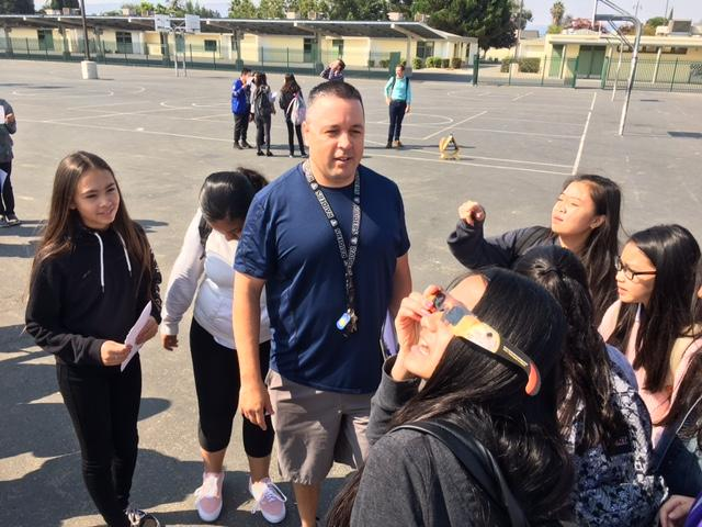 student looks to the sky with solar eclipse safe glasses while a teacher and students observe