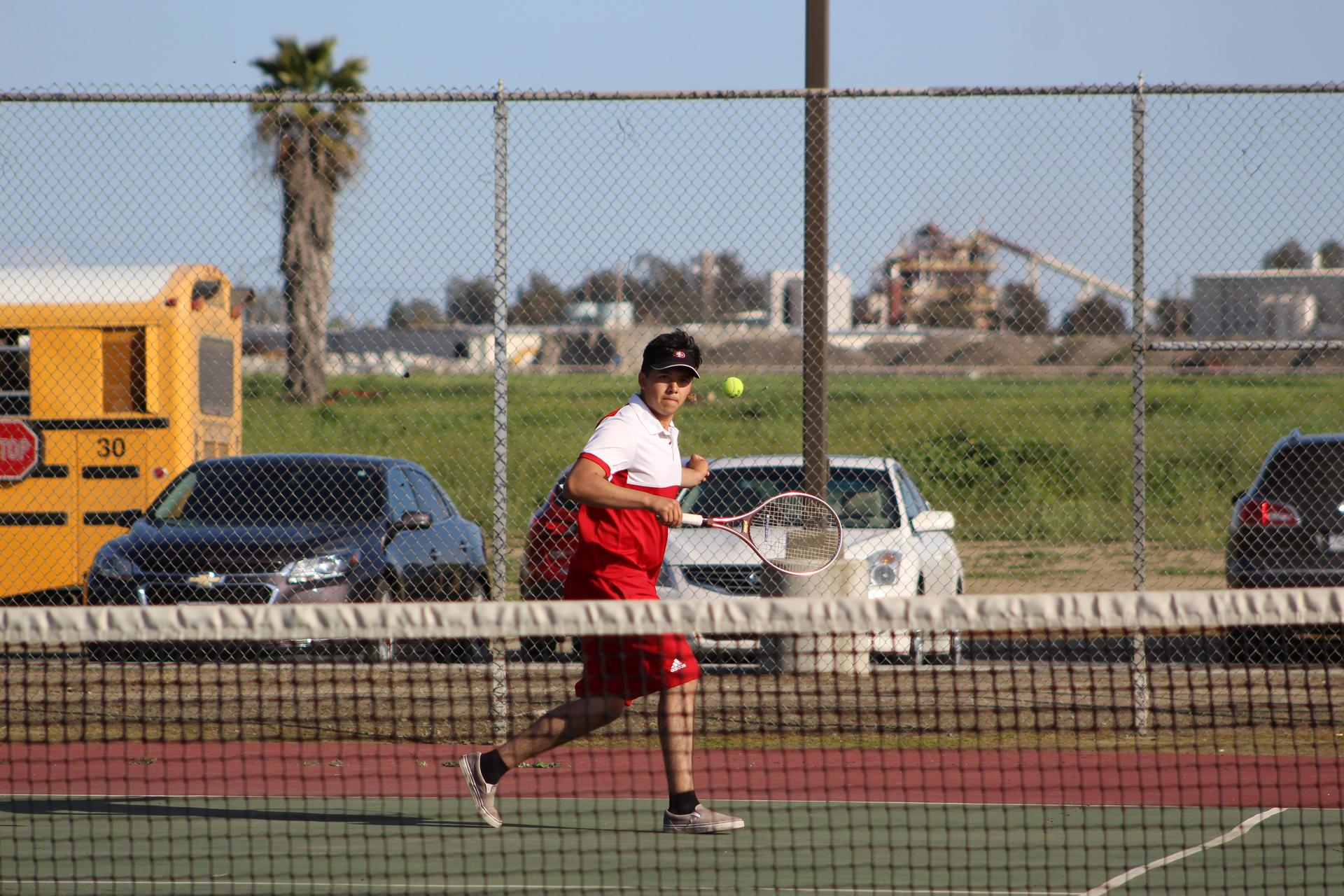 Boys playing tennis against Liberty