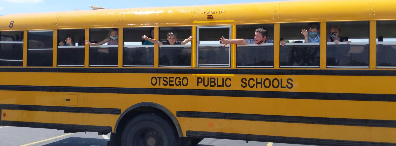 kids waving out of bus windows