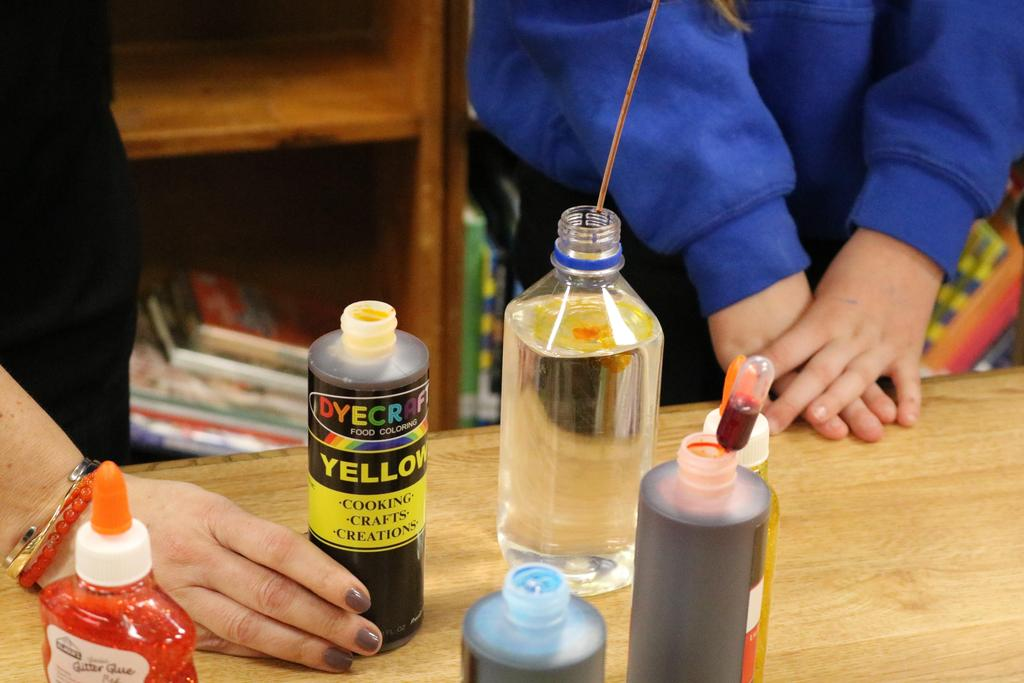Close up of putting food coloring and glitter glue into water bottle.
