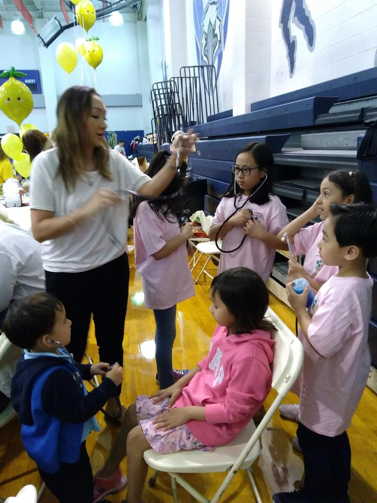 women teaching kids how to use a stethascope