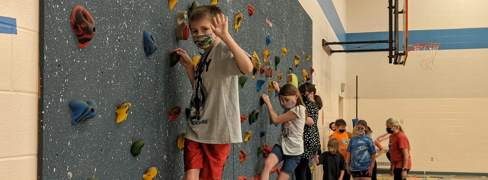 students climbing on rock wall