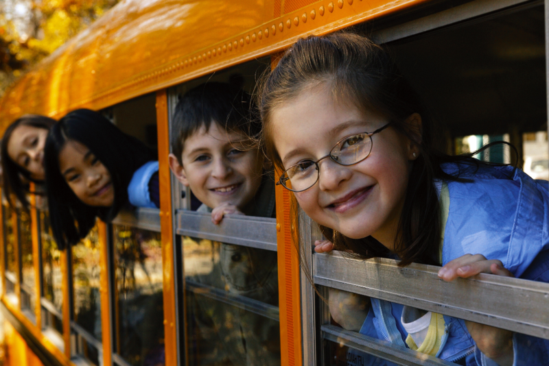 kids poking their heads out of the windows of a school bus