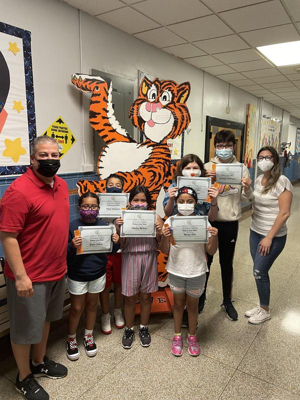 Students holding Student of the Week certificate with principal and teacher