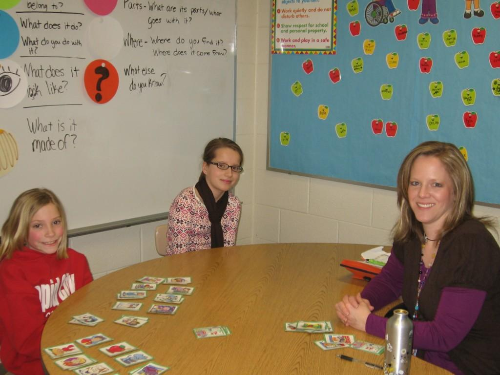 students and teacher playing educational card game