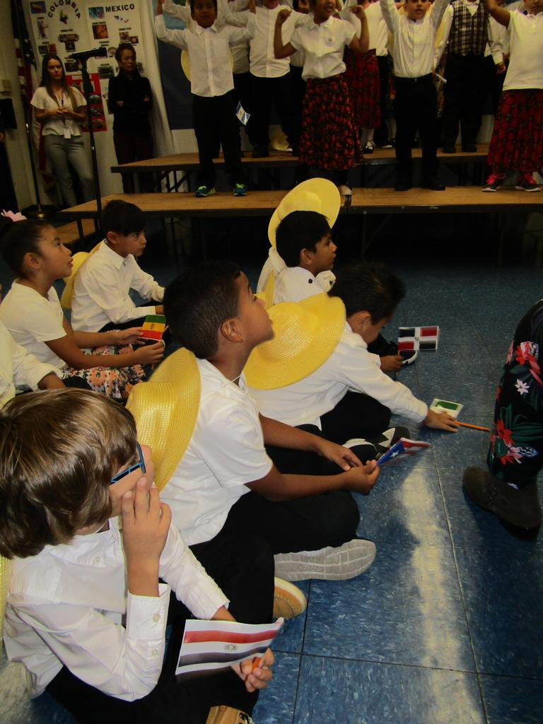 a group of children sitting on the floor while another group sings on stage
