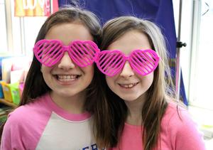Two Jefferson School students wear pink heart-shaped glasses during Valentine's Day activities.