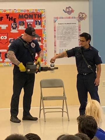 one firefighter holds the jaws of life and the other places a plastic bottle of water in the claw section