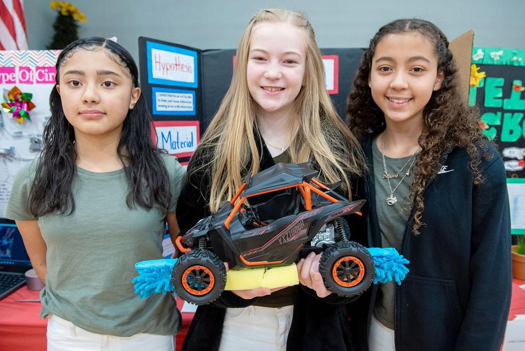 Posed photo of three students in front of their project, one of whom is holding a model car