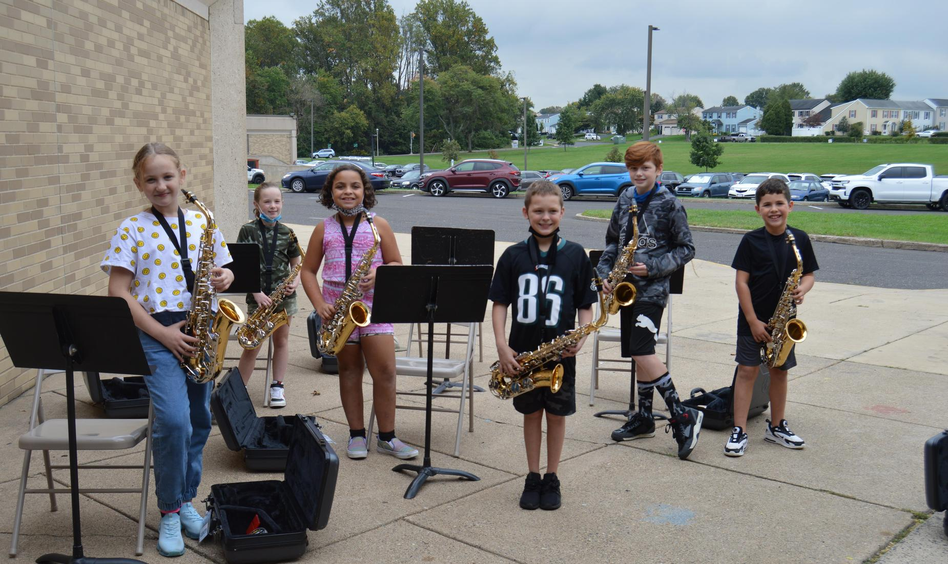 6 elementary students standing outside of their school during a beginner band lesson holding their saxophone.
