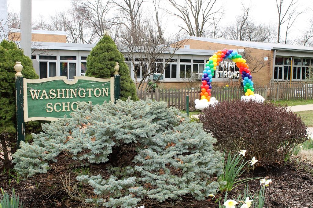 "Photo of Washington School sign with rainbow made of balloons and sign that says ""Stay Strong."""
