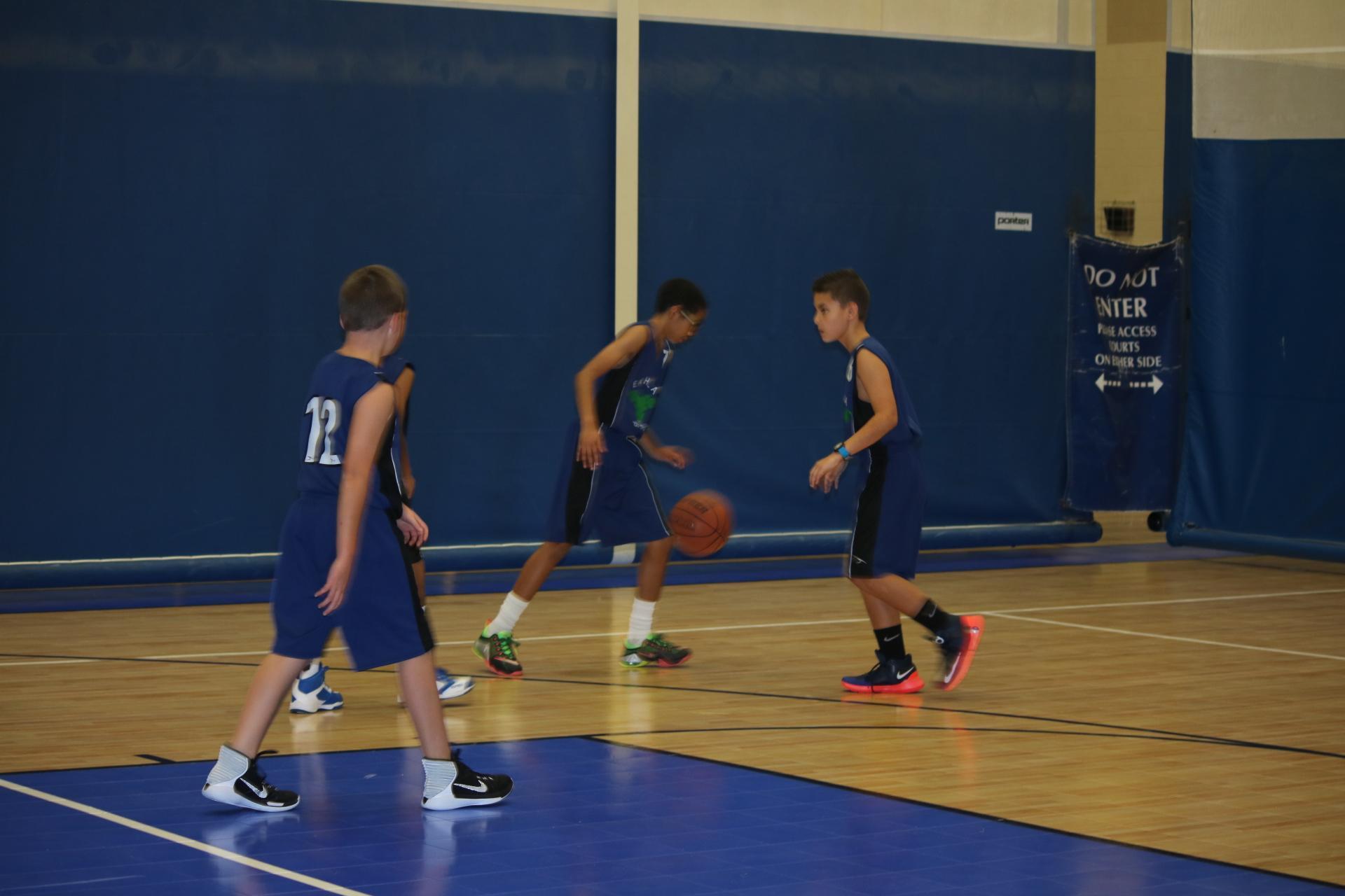 boys dribbling at basketball game