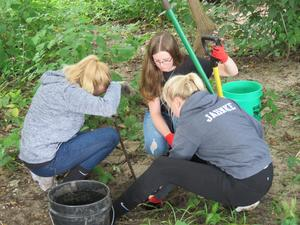 A group of TKHS students carefully removes broken glass from along the riverbank.