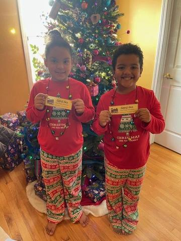 Sierra and Ellison holding tickets in matching pajamas