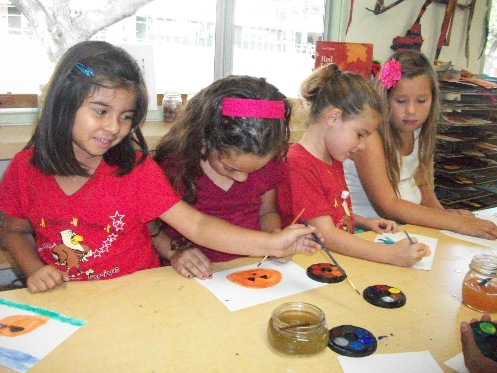 Children are exploring water colors in the classroom.