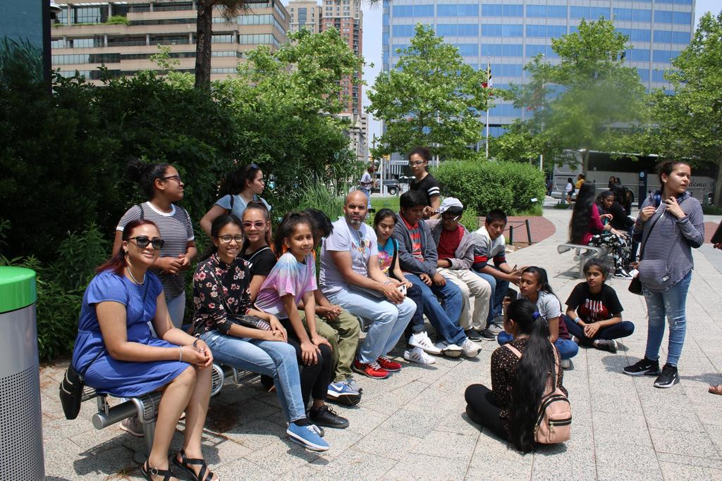 Students sitting by Baltimore inner Harbor.