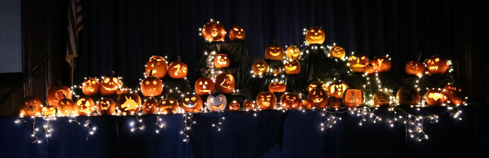 Carved pumpkins lit up in the darkened gym at McKinley on Halloween.