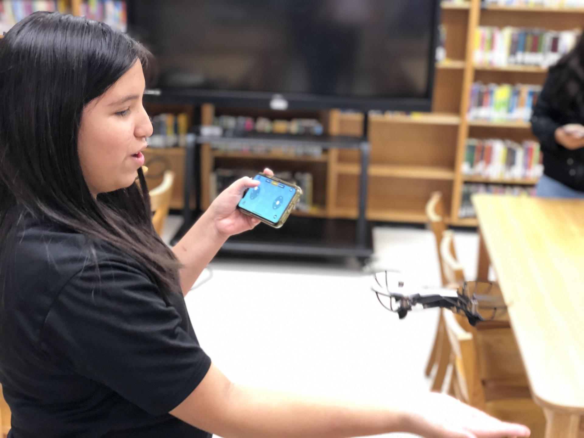 Student catches a drone in her hand.