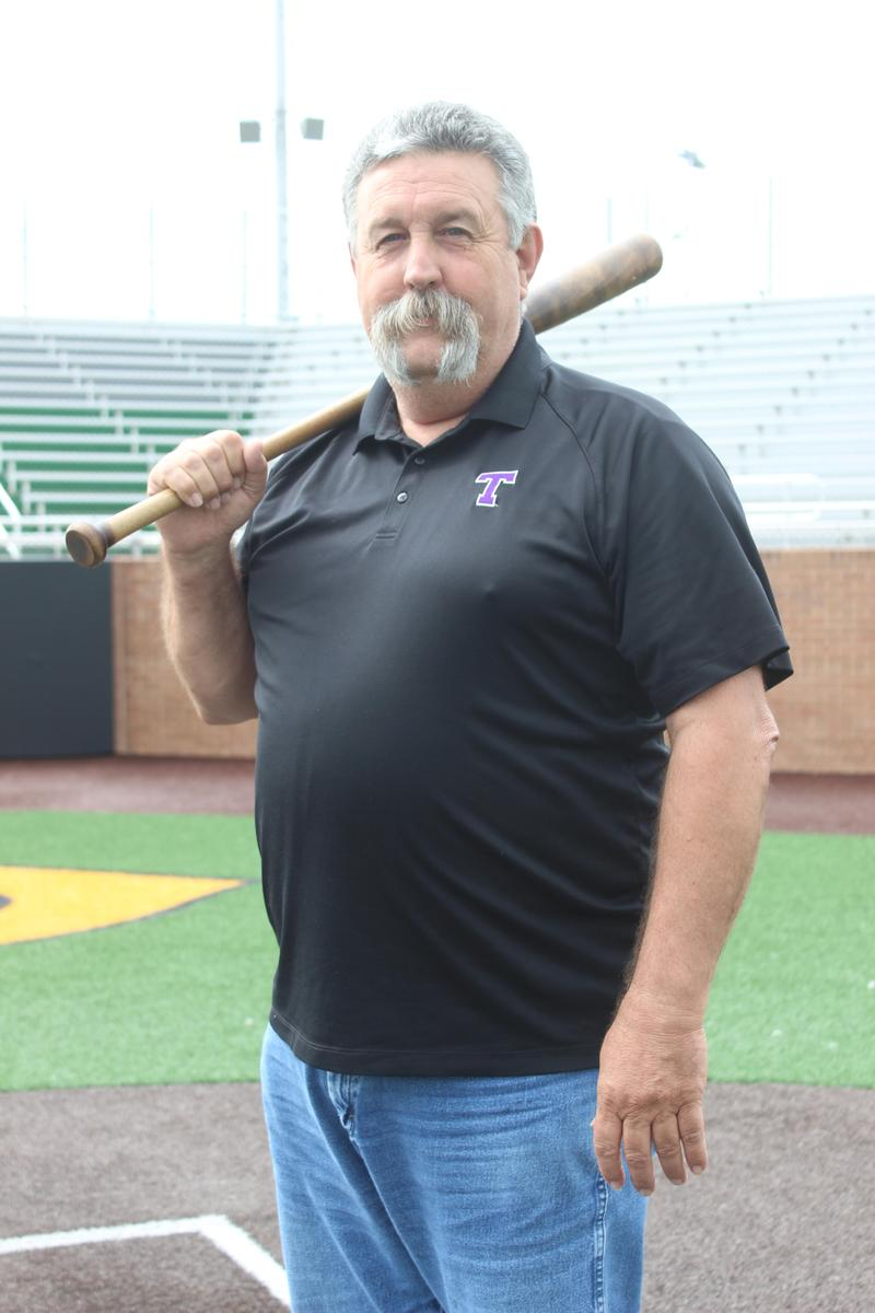 CHS teacher Dwayne Griffith holding a baseball bat