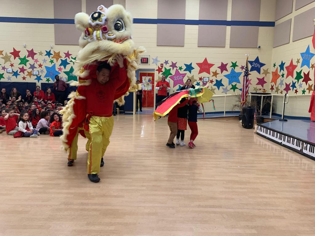 Chinese dragon performers next to the students who created their own dancing dragon