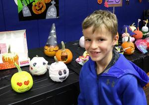 2nd grader poses in front of his decorated pumpkin for Wilson's annual Pumpkin Patch.