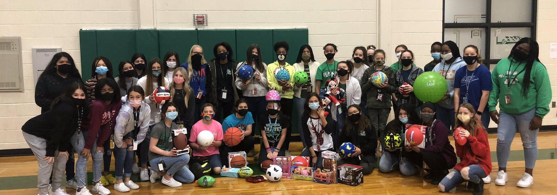large group of female athletes holding balls to be donated to those in need