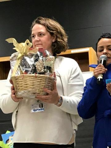 Teacher holding gift basket for raffle