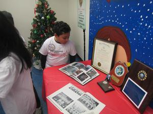 boy looking at the Veteran's table with photos, awards, etc. of service members