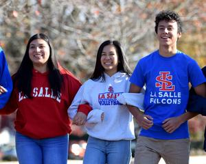 students walking arm in arm smiling in Falcon gear