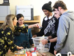 Westfield High School students prepare gift baskets for 4 refugee families who will enjoy a traditional Thanksgiving feast for the first time.  Pictured here are non-perishable food items lined up and ready to be put into basket.  Pictured here are two staff members and several WHS students readying basket of food.
