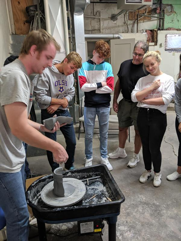 photo of students watching pottery demonstration