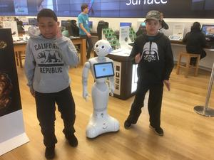 two students dancing with a robot in a store