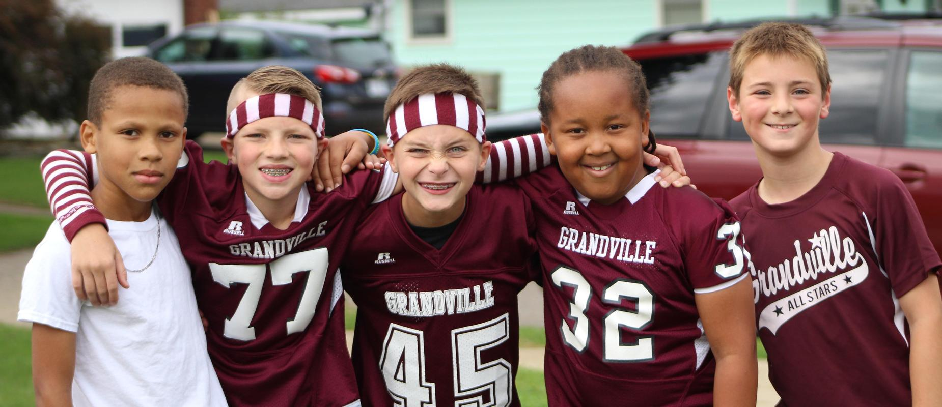5 elementary boys in maroon and white shirts stand with arms around each other outside