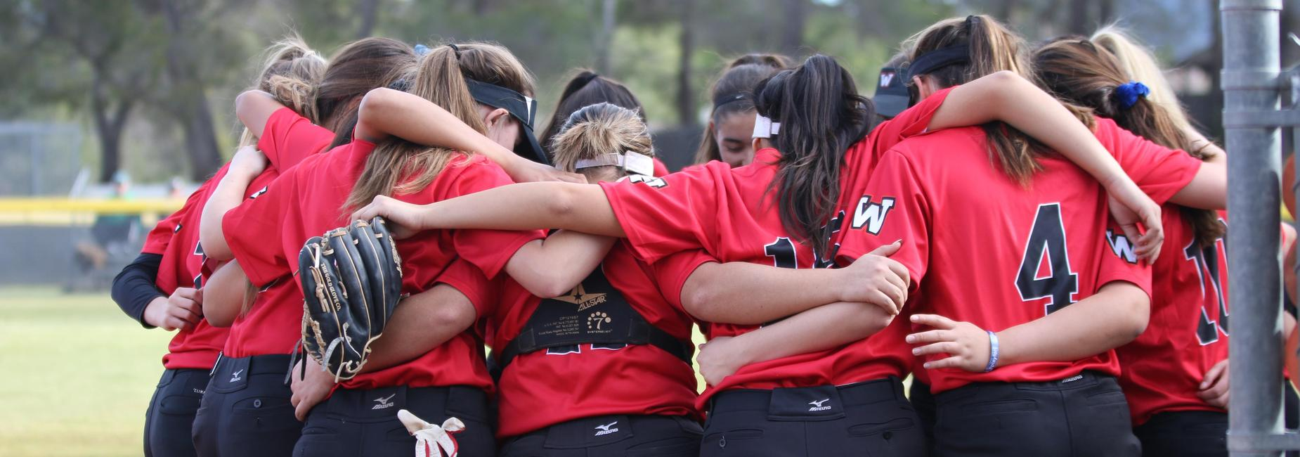 Photo of the softball team in a huddle.